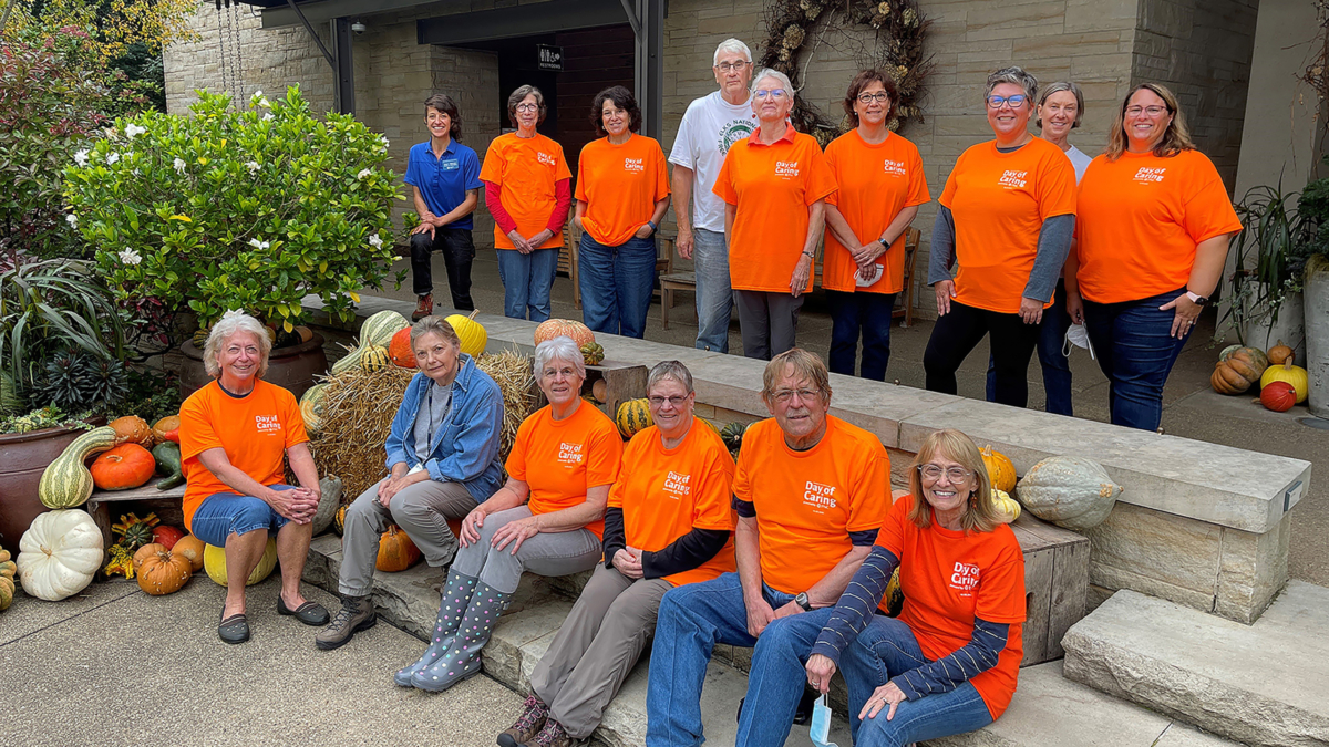 Group of adults outside wearing orange shirts.